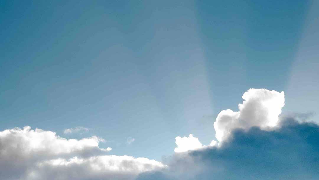 Sun lightbeam amidst cumulous clouds in sky